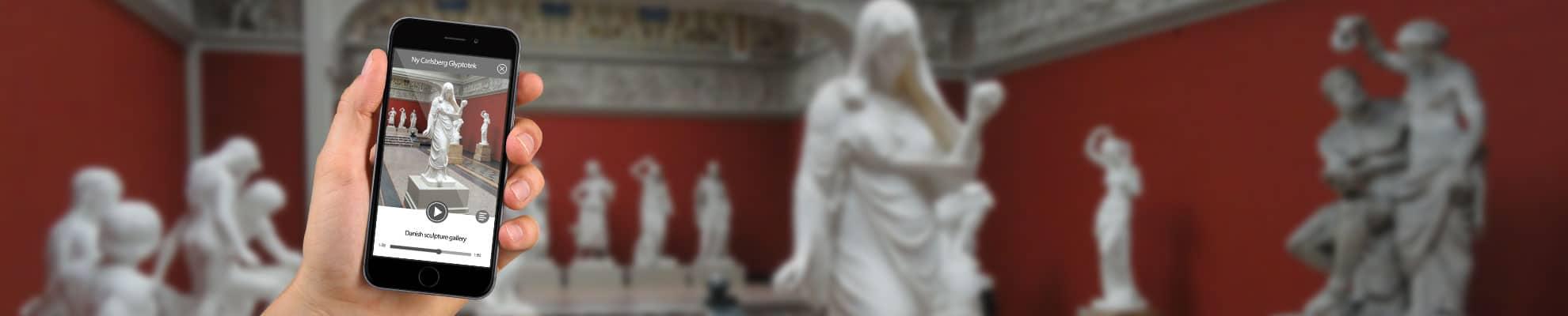 Museumsapp auf Smartphone vor Skulpturen