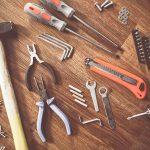 verschiedene-reparatur-werkzeuge-auf-holz-untergrund